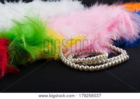 Different color bird feathers and white necklace lay on black background