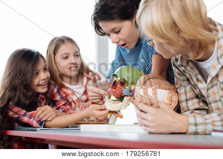 Would it bite. Communicative friendly smart boy helping his fellow students telling them interesting information about human skull while using a special model