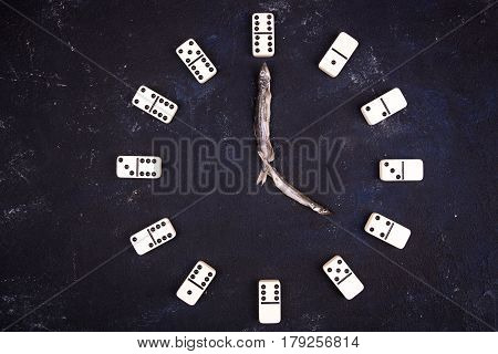 Hours from dominoes and arrows from fish on a dark concrete background. Four hours
