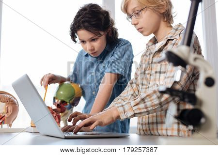 Typing correct data. Observant persistent intelligent guy looking determined while studying human anatomy using a laptop and special plastic models