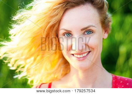 Happy middle-aged woman with blond hair smiling in backlight. The face of a beautiful girl with flying hair.