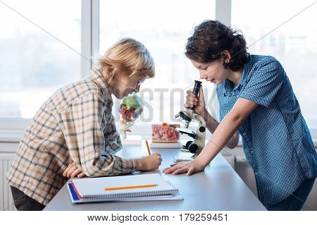 Write this down. Productive brilliant talented boy using a microscope conducting a research on bacteria while his classmate noting down the results