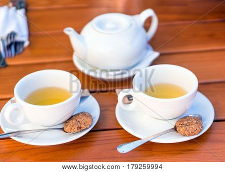 Two white cups of tea and spoons with biscuits teapot on a wooden table