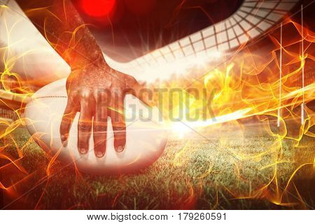 Composite image of close-up of sports player holding ball against ball of fire 3d