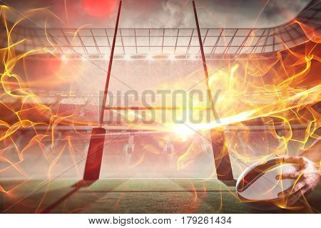 Composite image of close-up of of sports player holding ball against ball of fire 3d