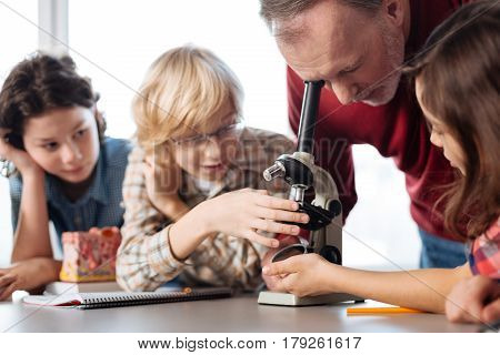 Just look at that. Enthusiastic hard working young scientists demonstrating some bacteria reactions using a microscope and waiting for their teachers opinion