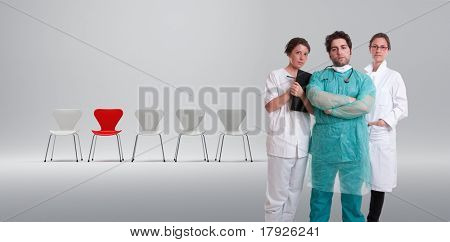 A surgeon and his team with a row of white chairs and a red one