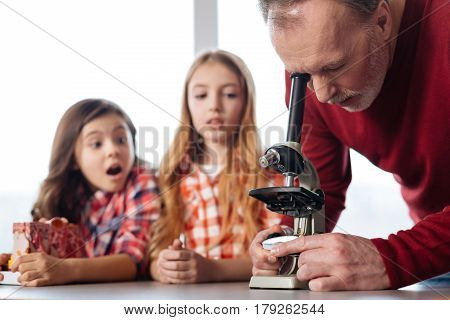 This is some magic. Dedicated focused cool teacher setting up a microscope for his students using it while conducting an in class experiment