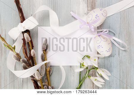 Easter whip willow twig and easter eggs on blue wooden table from above. Slovak and czech traditional easter background.