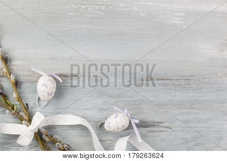 Traditional easter background. Pussy willow with easter egg and ribbon on wooden background top view.