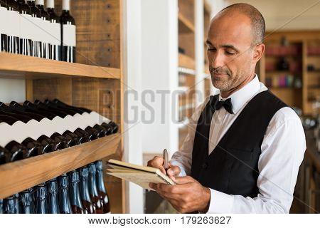 Sommelier writing inventory for red wine in stock in a shop. Multiethnic man taking notes in winery with wine bottles stacked in rows on the shelves. Bartender writing on a notebook.