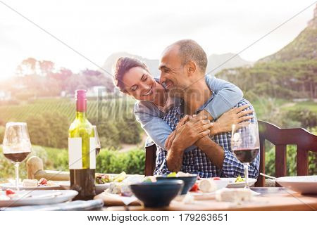 Happy mature couple looking at each other while hugging after lunch. Smiling couple in love sitting at dining table. Happy woman embracing from behind her boyfriend outdoor.