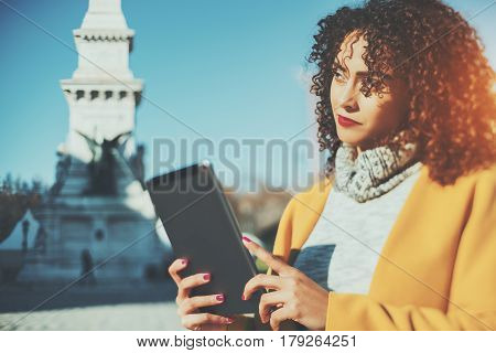 True tilt shift portrait of pensive curly woman with digital tablet on sunny street thoughtful Brazilian lady in yellow coat holding touch pad with copy space for your message or promotional content