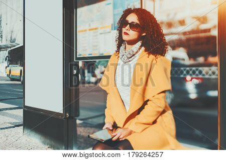 Adult curly beautiful brunette woman in sunglasses and yellow coat holding digital tablet and tired while waiting her bus inside of glass city bus stop with blank mock-up billboard next to her