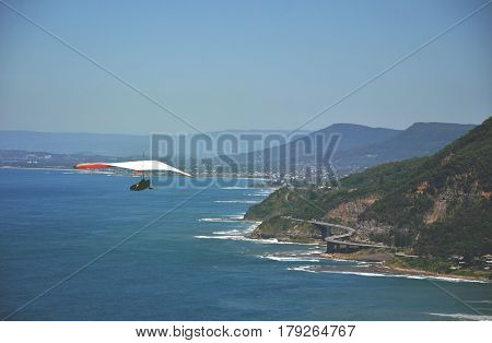 Hang glider soaring above the Sea Cliff Bridge along the Grand Pacific Drive on the New South Wales coast, Australia.