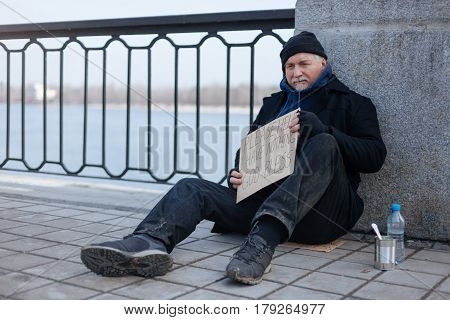 Need your help. Poor male person wearing dirty trousers and black coat leaning on the column while holding cardboard box in both hands