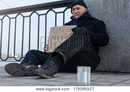 Unpleasant situation. Grey-haired man wearing dirty clothes expressing problems on face while sitting near tin for coins