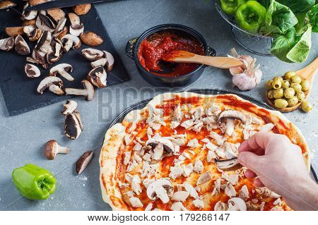 Pizza preparation raw dough surrounded by ingredients. Male hand puts the mushroom on the pizza dough.