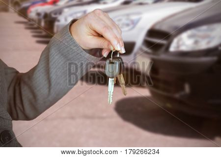 Person handing keys to someone else against cropped image of cars parked in row