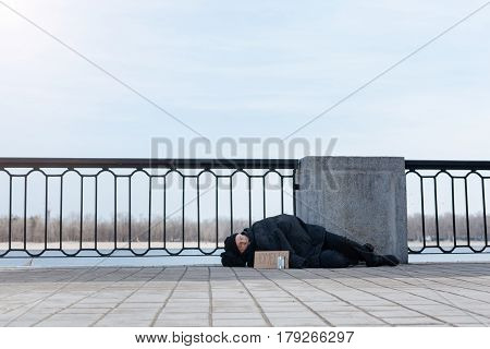 Time for sleep. Full length photo of homeless male lying on the street wrapping himself with jacket while leaning on the column