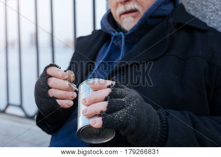 That is tasty. Old bearded man sitting outdoors wearing black coat while pressing his lips