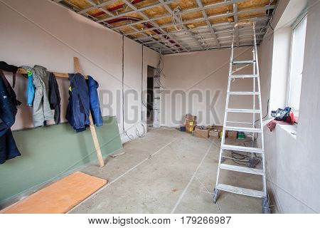 The clothes of workers in the room of apartment during the remodeling renovation and construction