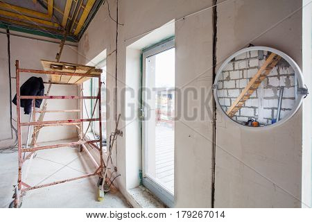 Ladder in the mirror and parts of scaffolding during on the remodeling renovation and construction of apartment with big windows