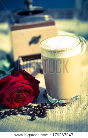 Latte macchiato with red rose and coffee mill in the background
