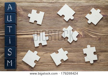 Concept of Autism awareness. Autism Spectrum Disorder (ASD). Wooden cubes with word AUTISM and puzzle pieces on a wooden background top view flat lay. poster