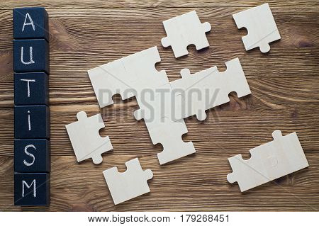 Autism awareness. Black wooden cubes with word AUTISM and puzzles on a wooden background top view flat lay. Concept of autism word. Autism Spectrum Disorder (ASD).