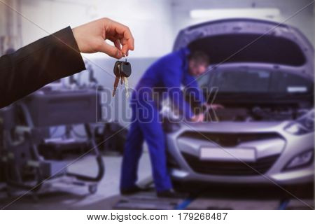 Couple receiving car keys by a dealer against mechanic leaning on a car looking at the engine