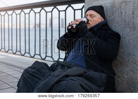 Good people help. Exhausted man covering his knees with jacket holding thermo cup near mouth keeping eyes closed