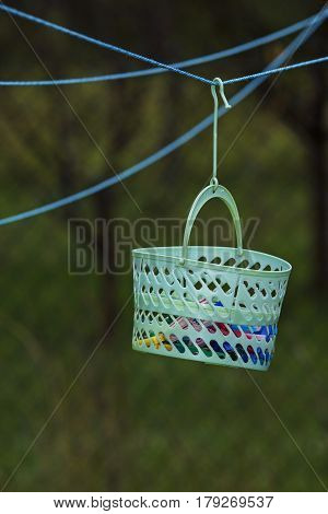 Basket full of clothes pins isolated on rope