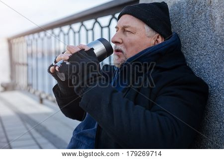 Imagine happy life. Profile of serious male person wearing cap and gloves leaning on the column while drinking tea