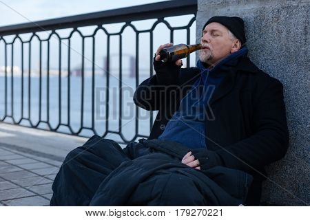 Grieve for previous life. Homeless man covering his knees with clothes keeping eyes closed while holding glass bottle in right hand