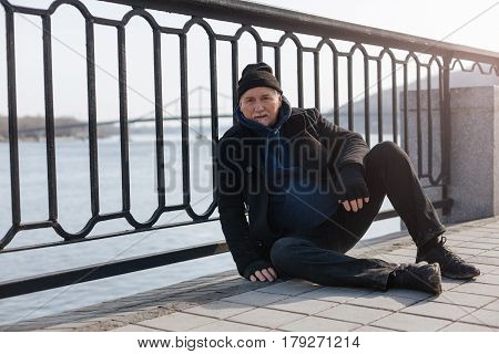 Sit and think. Full length photo of kind man wearing casual clothes putting left hand on the knee while looking straight