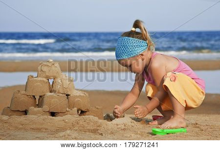 The child builds a sand castle on the beach toy shovel