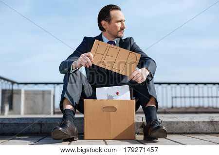 Box with my things. Jobless male person wearing smart costume sitting on the pavement while looking sideways