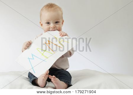 Mother - first word. Infant boy holding big postcard with a sign mama. Copy space. Mothers day. Boy smiling