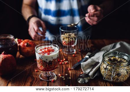 Pomegranate Dessert and Guy Prepare Second Portion on Backdrop. Series on Prepare Healthy Dessert with Pomegranate, Granola, Cream and Jam