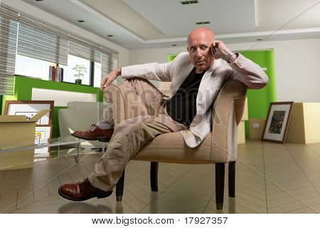 Mature man slumped on an armchair talking on the cell phone in a home interior on a removal day
