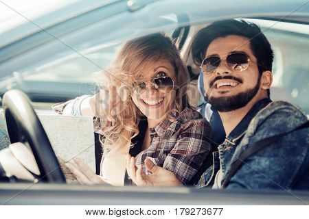 Smiling man and woman using map on roadtrip.Leisureroad trip travel and people concept.