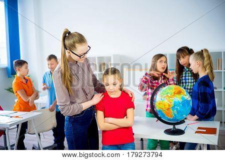 Teacher calms stressed girl and hugs her