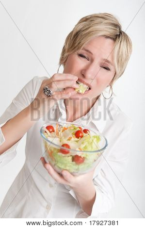 Woman with an unhappy face tasting a salad