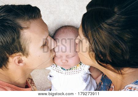 Affectionate happy young couple lying down on the floor are kissing their sleeping newborn baby girl on her cheeks situated in the middle.