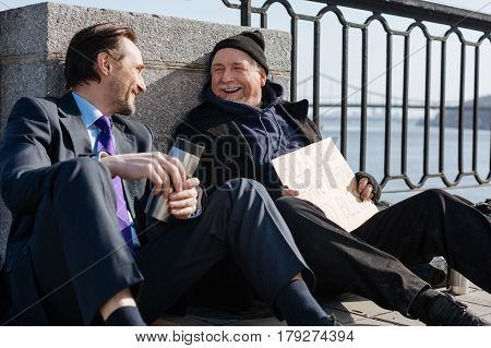Enjoy your life. Homeless pensioner wearing warm clothes leaning on the wall while keeping wide smile on face