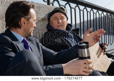 I can help you. Attentive elderly man wearing black cap wrinkling his forehead while listening new friend