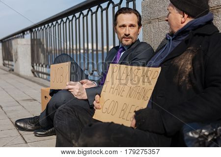 Hope for better future. Unhappy office worker wearing costume looking at his interlocutor while holding letter plate
