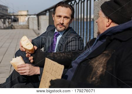 Have a break. Two men sitting in semi position outdoors when younger person wearing costume, giving half of loaf to his new friend