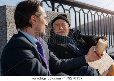 Feeling happiness. Positive delighted bearded male person wearing warm clothes stretching his hand while looking at new friend
